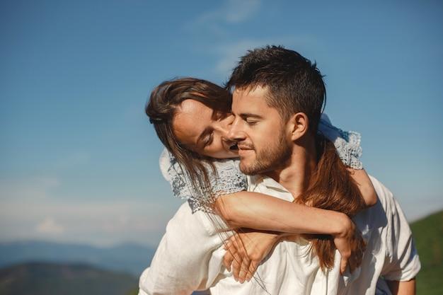 Hombre y mujer en las montañas. joven pareja de enamorados al atardecer. mujer con un vestido azul.