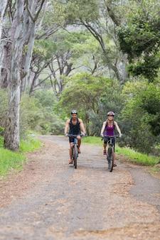 Hombre y mujer montando bicicleta en el bosque