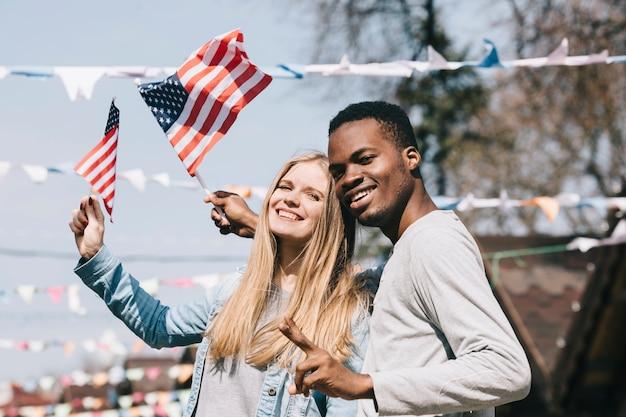 Hombre y mujer multiétnica con banderas americanas