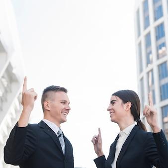 Hombre y mujer de negocios apuntando hacia arriba