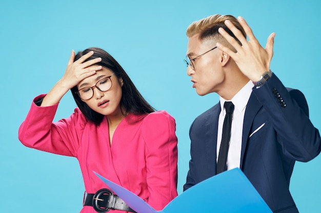 Hombre y mujer de negocios asiáticos mirando documentos corporativos