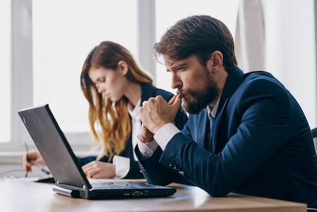 Hombre y mujer de negocios sentados en un escritorio con una computadora portátil profesionales de las finanzas de la comunicación