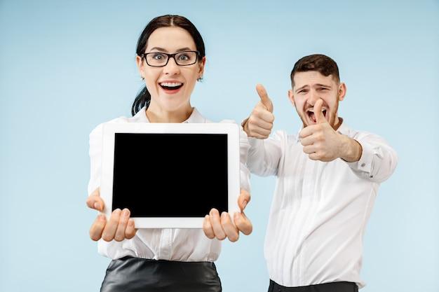 El hombre y la mujer de negocios sorprendidos sonriendo en un espacio azul y mostrando la pantalla vacía de la computadora portátil o tableta