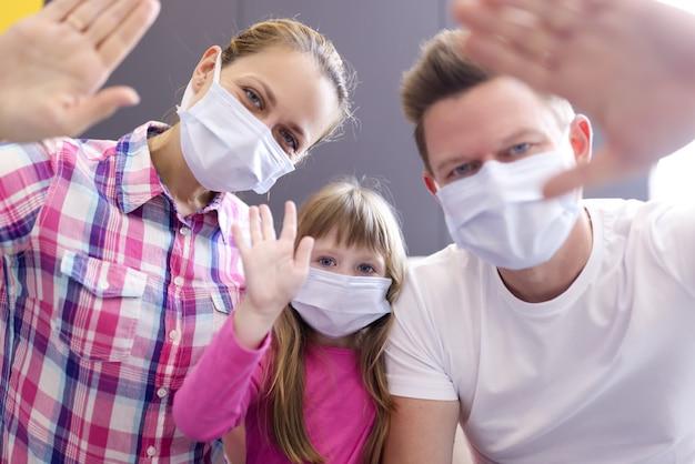 Hombre, mujer y niña con máscaras médicas protectoras en la cara saludando frente a la computadora portátil