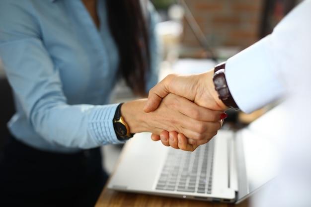 Hombre y una mujer en la oficina se dan la mano