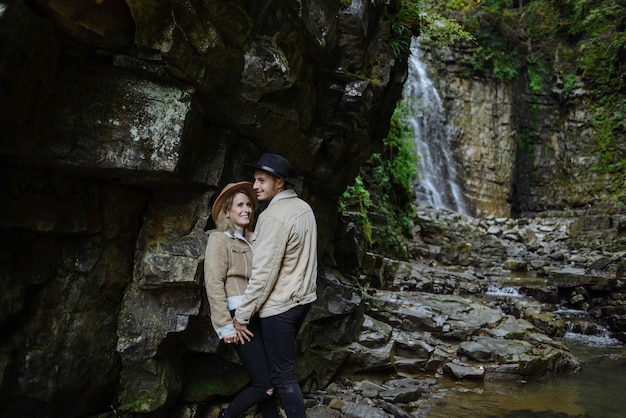 El hombre y la mujer se paran y se abrazan en las rocas, cerca del árbol, el bosque y el lago. paisaje de una antigua cantera de granito industrial. cañón.
