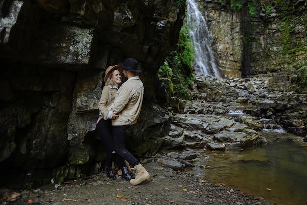 El hombre y la mujer se paran y se abrazan en las rocas, cerca del árbol, el bosque y el lago. paisaje de una antigua cantera de granito industrial.
