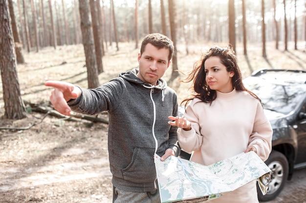 Hombre y mujer perdidos en el bosque. están parados con un mapa y no saben a dónde ir después.