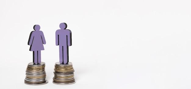 Hombre y mujer de pie sobre montones de monedas