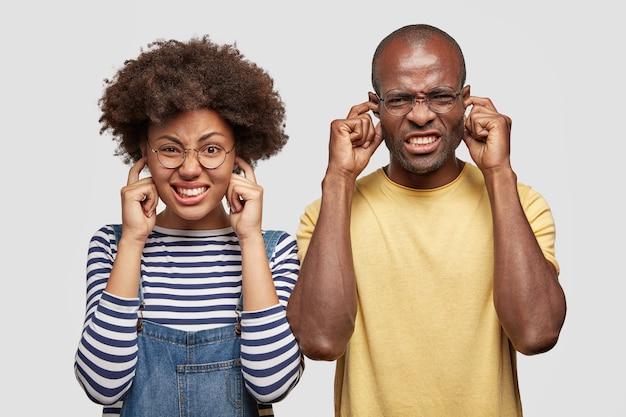 Hombre y mujer de piel oscura desesperados tapan los oídos y aprietan los dientes con irritación
