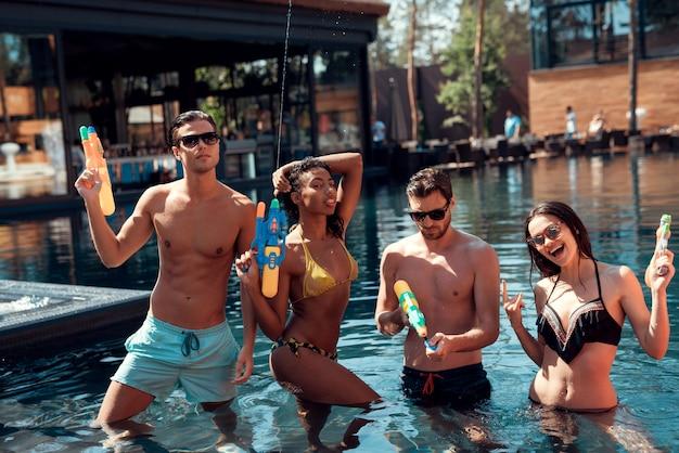 Hombre y mujer en piscina con pistolas de agua