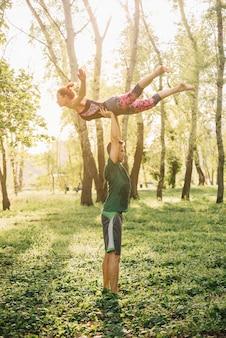 Hombre y mujer practicando acroyoga en jardín