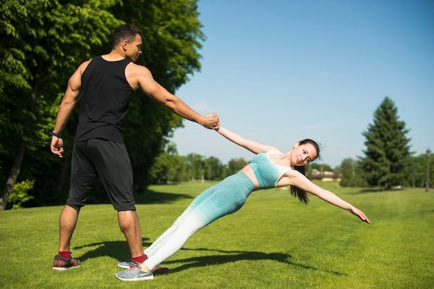 Hombre y mujer practicando yoga al aire libre
