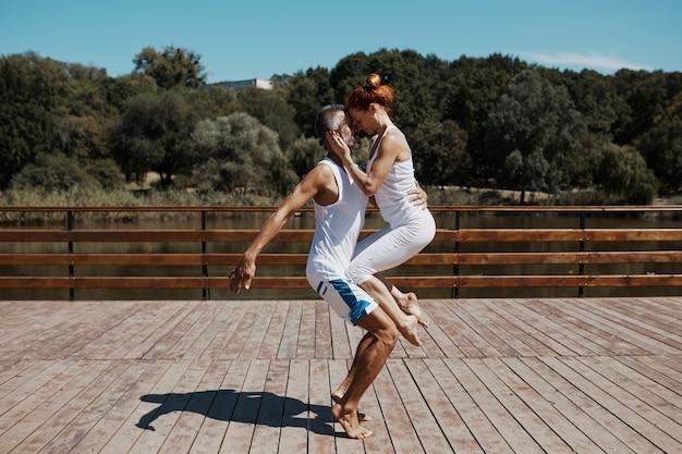 Hombre y mujer practicando yoga avanzado en el parque
