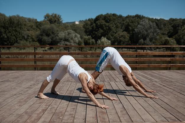 Hombre y mujer practicando yoga en el parque