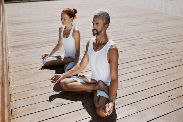 Hombre y mujer practicando yoga relajante en el parque