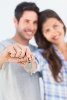 Hombre y mujer presentando una llave con un llavero de la casa
