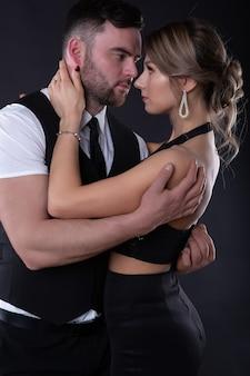 Hombre y una mujer que cierran los ojos con placer se abrazan tiernamente