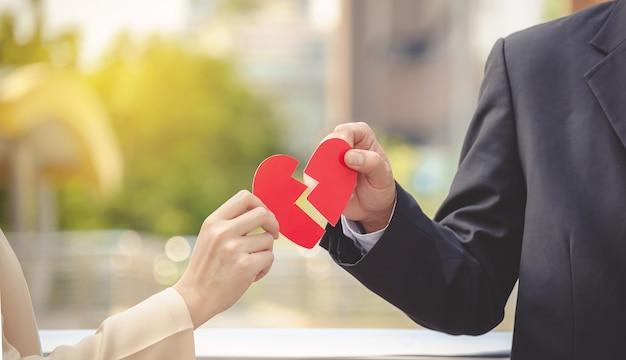 Hombre y mujer que separan un corazón de papel rojo. el concepto de amor no correspondido. oído roto