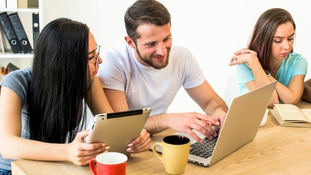 Hombre y mujer que usan aparatos electrónicos sentados cerca de su amigo leyendo un libro