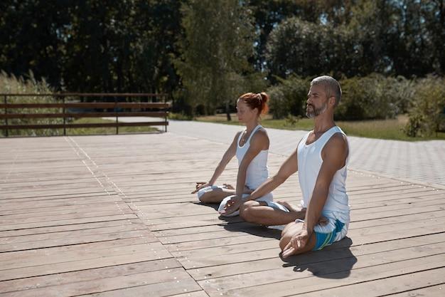 Hombre y mujer en ropa blanca practicando yoga al aire libre