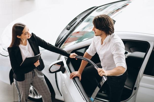 Hombre con mujer en una sala de exposición de automóviles elegir un automóvil