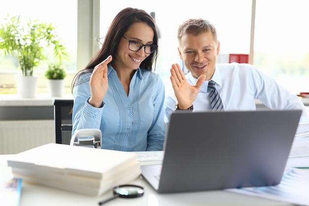 El hombre y la mujer saludan al interlocutor con la mano en la llamada en línea en la computadora portátil