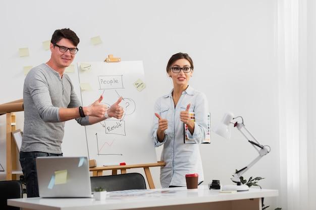 Hombre y mujer seguros mostrando signo bien junto a un diagrama