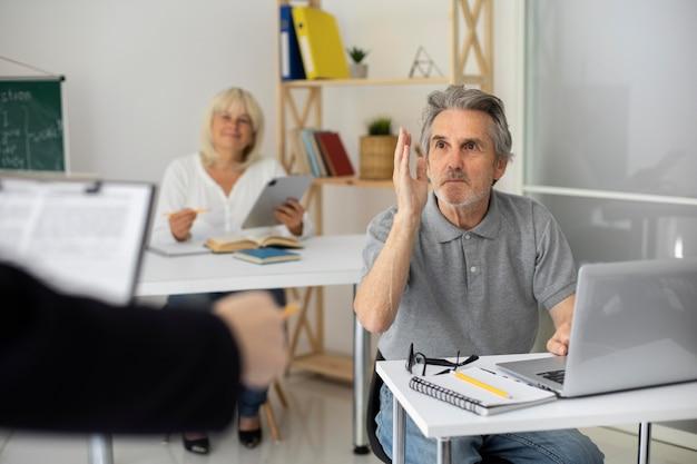 Hombre y mujer senior prestando atención en clase