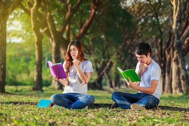 Hombre y mujer sentada y leyendo un libro en el parque