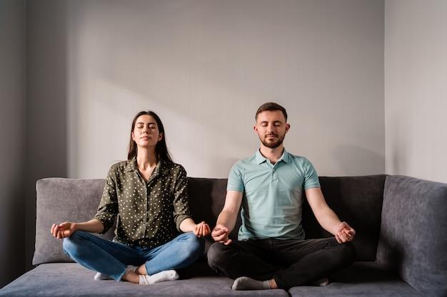 Hombre y mujer sentada en el sofá en postura de loto