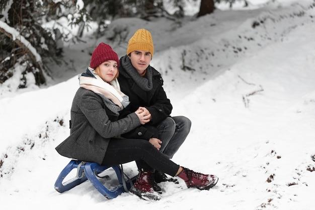 Hombre y mujer sentada en el trineo
