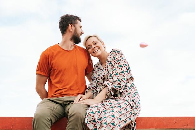 Hombre y mujer sentados felices sobre una tabla de madera mirando a un globo corazón rosa volando en el cielo