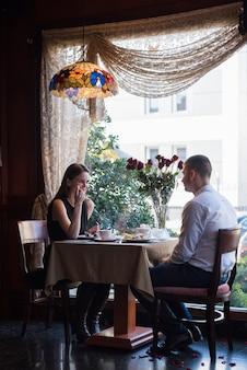 Hombre y mujer sentados a la mesa con postres, bebidas y flores en café