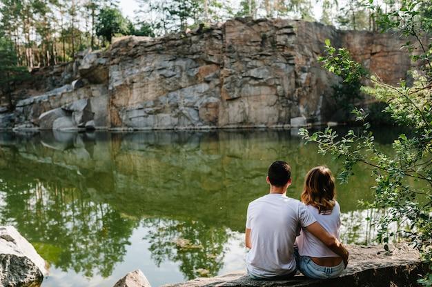 El hombre y la mujer se sientan en piedra cerca del lago en el fondo de grandes rocas