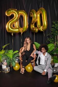 Hombre y mujer sonriendo y globos de año nuevo 2020