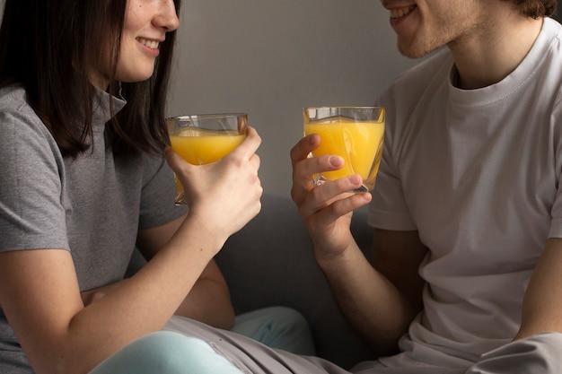 Hombre y mujer sonriendo y sosteniendo jugo de naranja
