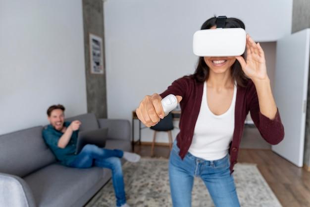 Hombre y mujer sonriente divirtiéndose en casa con casco de realidad virtual
