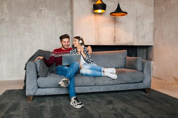 Hombre y mujer sonrientes jóvenes sentados en casa en invierno mirando en la computadora portátil con expresión de cara feliz, usando internet