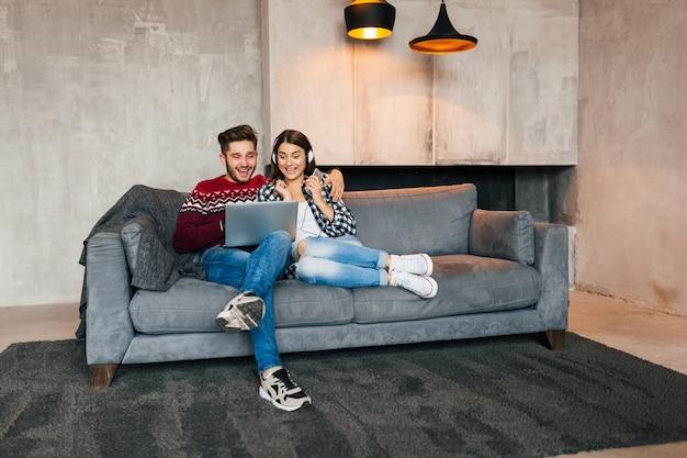 Hombre y mujer sonrientes jóvenes sentados en casa en invierno mirando en la computadora portátil con expresión de la cara sorprendida, usando internet, pareja en el tiempo libre juntos, emoción feliz y positiva
