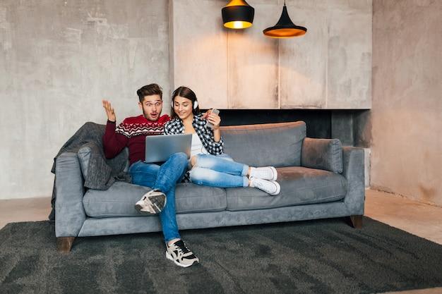 Hombre y mujer sonrientes jóvenes sentados en casa en invierno mirando en la computadora portátil con expresión de cara de sorpresa sorprendida, usando internet, pareja en el tiempo libre juntos, emoción feliz y positiva