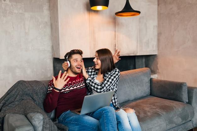 Hombre y mujer sonrientes jóvenes sentados en casa en invierno sosteniendo en la computadora portátil escuchando auriculares con expresión de la cara sorprendida, usando internet, pareja en el tiempo libre juntos, feliz