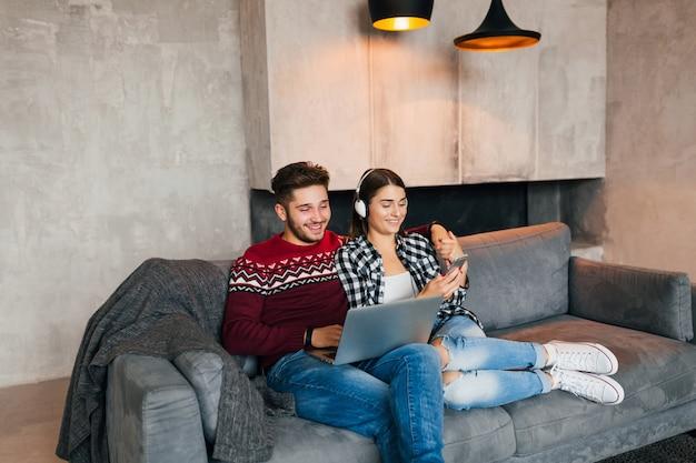 Hombre y mujer sonrientes jóvenes sentados en casa en invierno, trabajando en la computadora portátil, sosteniendo el teléfono inteligente, escuchando auriculares, pareja en el ocio pasando tiempo en línea, autónomo, citas