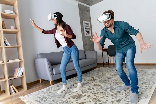 Hombre y mujer sonrientes que se divierten en casa con casco de realidad virtual