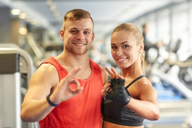 El hombre y la mujer sonrientes que muestran la mano bien firman en el gimnasio