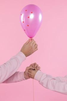 Hombre y mujer sosteniendo globo violeta con adornos corazones e hilo