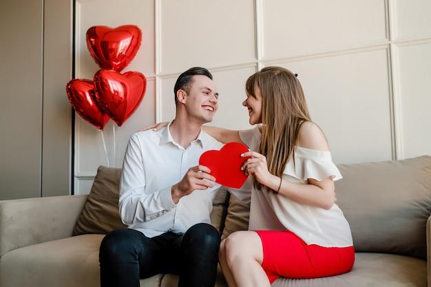 Hombre y mujer con tarjeta de san valentín en forma de corazón rojo y globos en casa en el sofá