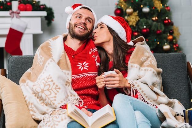 Hombre y mujer con taza y libro en sofá