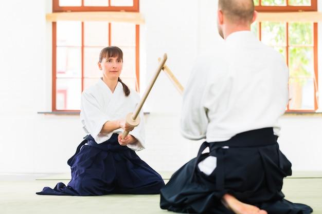 Hombre y mujer teniendo lucha de espadas del aikido.