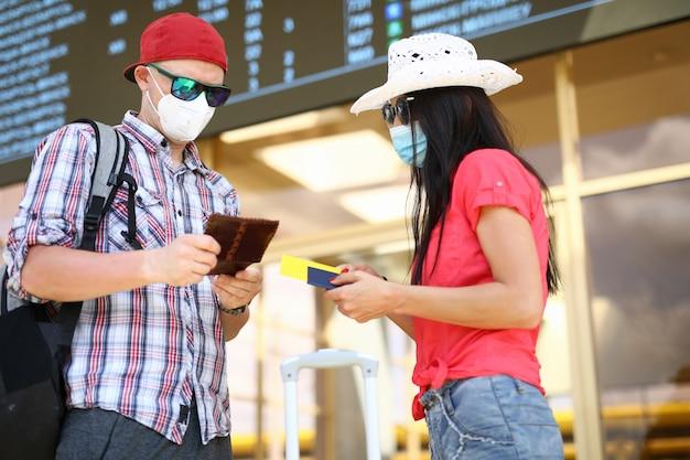 Hombre y mujer tienen pasaporte de fondo del aeropuerto agaist con retrato de boleto de avión